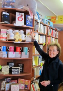 owner with local author shelf bookstore
